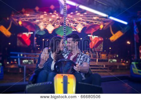 Affectionate couple sitting in bumper car at  amusement park
