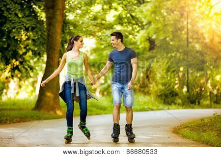 Smiling couple holding hands riding rollerblades