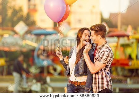 Young romantic man in love feeding his girlfriend with cotton candy