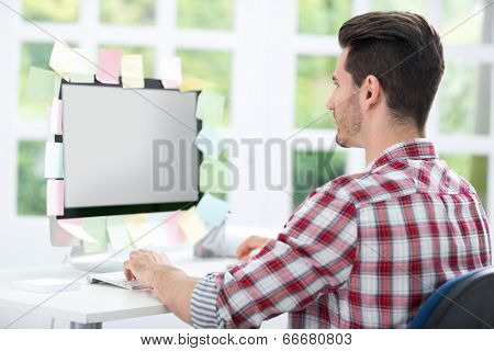 Man looking at a computer monitor with sticky note on it