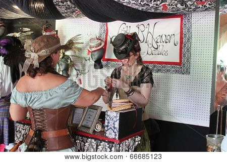 MUSKOGEE, OK - MAY 24: A woman in historical costume sells her crafts at the Oklahoma 19th annual Renaissance Festival on May 24, 2014 at the Castle of Muskogee in Muskogee, OK.