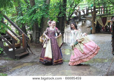 MUSKOGEE, OK - MAY 24: Women dressed in historical costume walk around the village at the Oklahoma 19th annual Renaissance Festival on May 24, 2014 at the Castle of Muskogee in Muskogee, OK.