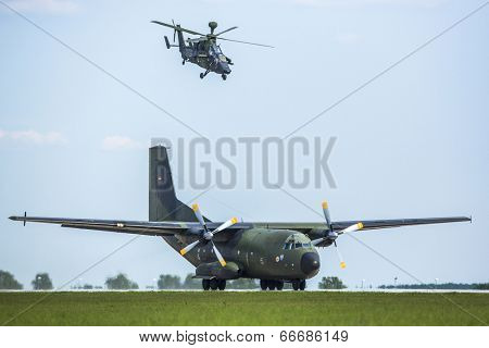 BERLIN, GERMANY - MAY 21, 2014: Transport plane C-160 Transall starts and Tiger combat helicopter go behind machine in position and secure launch from the air, demonstration at ILA Berlin Air Show.