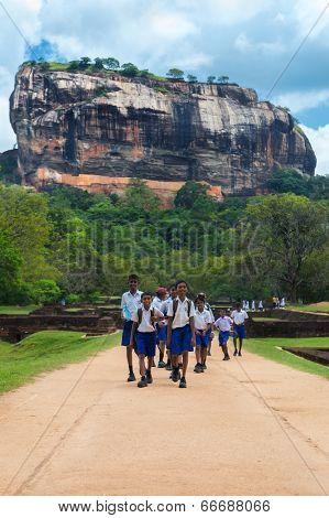 SIGIRIYA, SRI LANKA - 28 FEBRUARY, 2014: Group of unidentified school students walking in garden complex with rock of Sigiriya as backdrop . Sigiriya is UNESCO listed World Heritage Site.