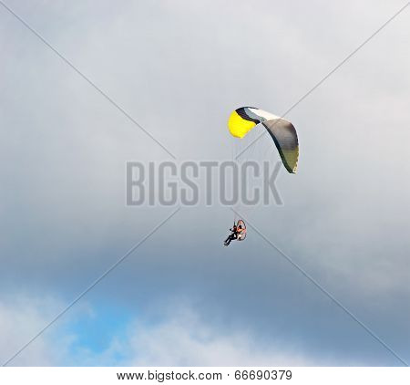 Yellow And Black Glider Under Clouds