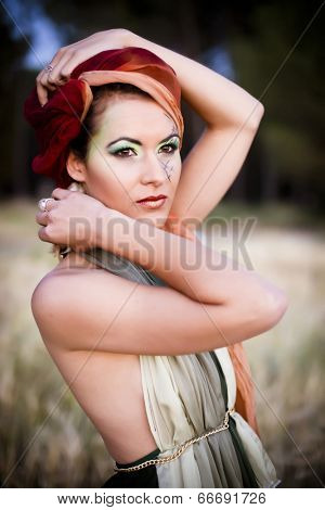 Soft colored portrait of a fashion model with a tribal style. Shoot at dusk for a melancholic effect.