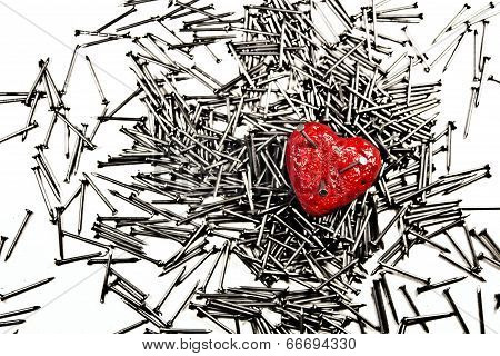 Red Heart On Pile Of Iron Nails, Pierced By A Three Nails