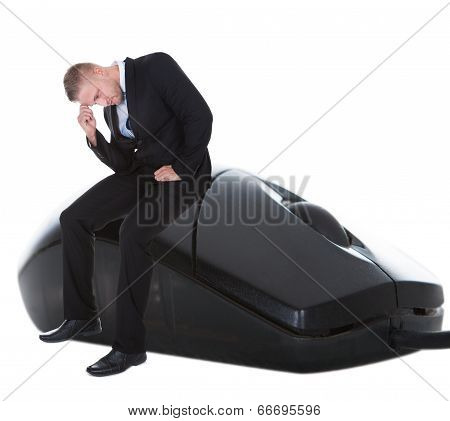 Worried Businessman Sitting On A Computer Mouse