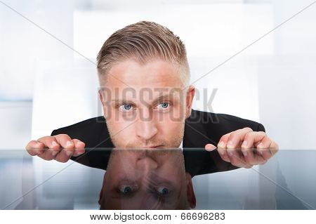 Businessman Peering Furtively Over The Top Of His Desk