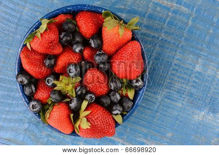 High angle shot of strawberries and blueberries in a blue enamelware bowl. The bowl is on a rustic wooden farmhouse style kitchen table painted blue.
