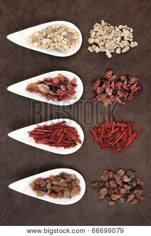 Frankincense, myrrh, sandalwood and fragrant rose flower petals over handmade lokta paper background.