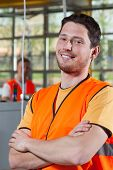 stock photo of vest  - Portrait of a smiling factory worker in orange protective vest standing with arms crossed - JPG
