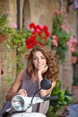 picture of scooter  - Young beautiful italian woman sitting on a italian scooter in Tuscany street - JPG