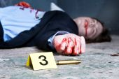 stock photo of gruesome  - Empty cartridge found on a crime scene with a yellow placard with number three and a dead body in the background - JPG
