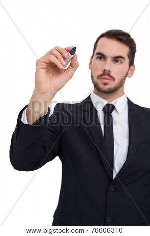 Thoughtful businessman writing with marker on white background