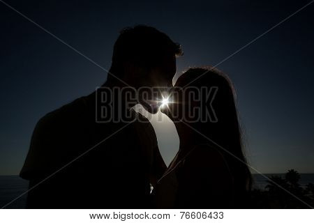 Cute couple kissing in silhouette as the sun is going down