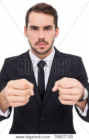Frustrated businessman with closed fists looking at camera on white background