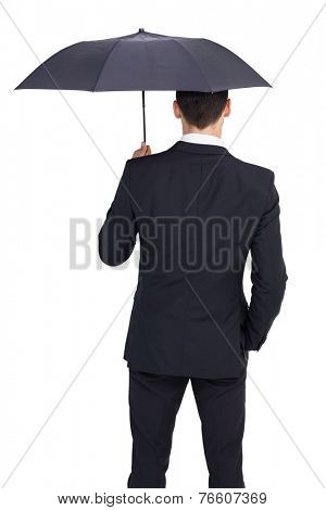 Rear view of businessman sheltering with umbrella on white background