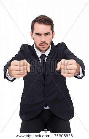 Angry businessman standing with clenched fists on white background
