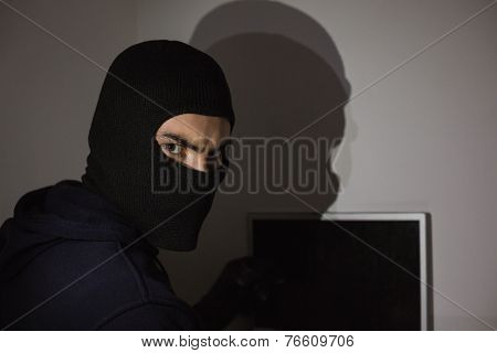 Hacker in balaclava hacking laptop while looking at camera in house