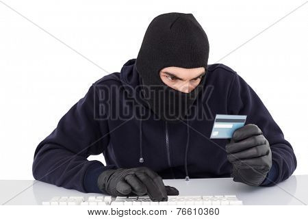 Focused burglar using computer and debit card on white background