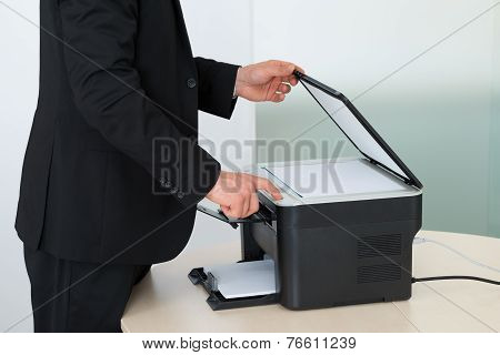 Midsection Of Businessman Using Photocopy Machine In Office