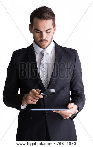 Concentrated businessman using magnifying glass on white background