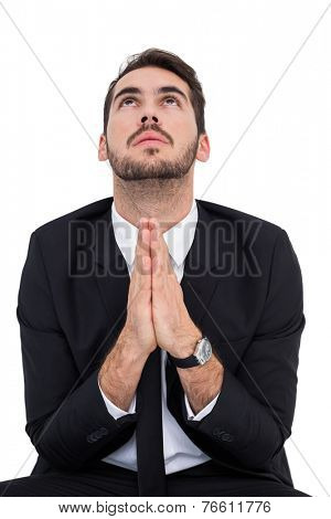 Elegant businessman with hands together prying on white background