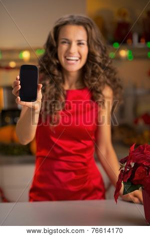 Closeup On Happy Young Housewife Showing Cell Phone In Christmas
