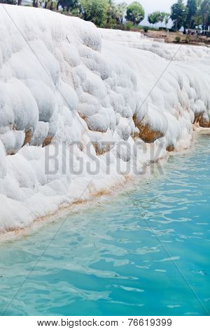 Carbonate travertines with blue water - unique nature wonder in Pamukkale, Turkey