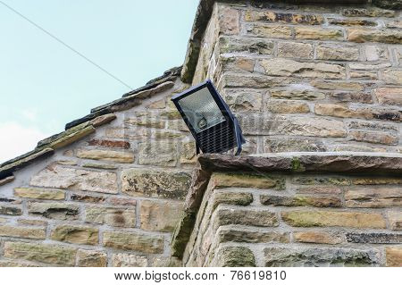 Home Security Light Mounted On The Corner Of A Rural Stone Cottage.