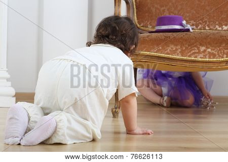 Little boy sitting on floor and looks at girl in purple skirt behind sofa