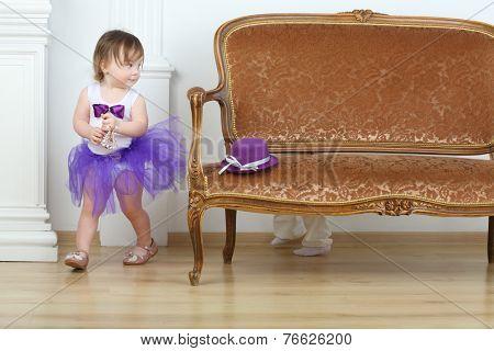 Little girl in purple skirt running away from boy around sofa
