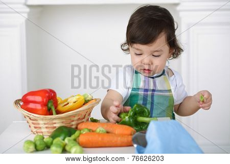Little boy in kitchen apron playing with vegetables at table