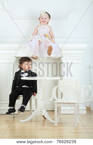 Little boy in black suit sitting on chair and girl in white dress on ledge at top