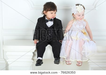 Beautiful little girl in white long dress with boy in a black tuxedo sitting on white ledge