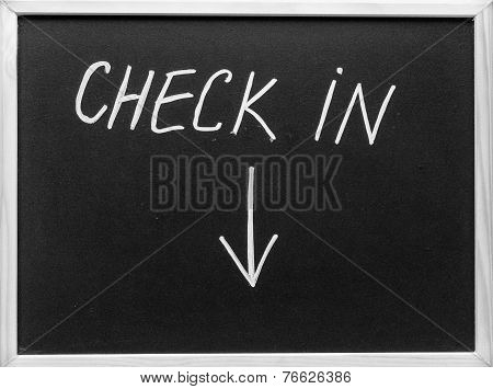 Check In Message And Arrow Pointing Downwards Written With White Chalk On Blackboard