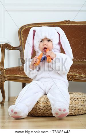 Little boy in costume bunny sitting on pouf with carrot