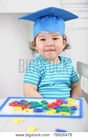 Portrait of laughing child in blue graduation hat sitting at table with children magnetic board with colored letters