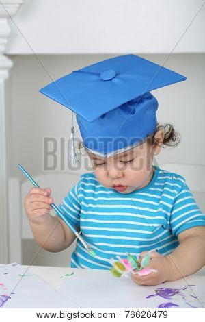 Portrait of serious little boy in blue graduation hat boy with paint and brush in hand at table