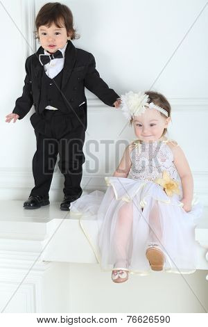 Beautiful little girl in white long dress with boy in a black suit on white ledge