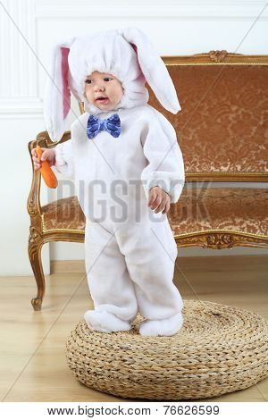 Little boy in costume bunny standing on pouf with carrot
