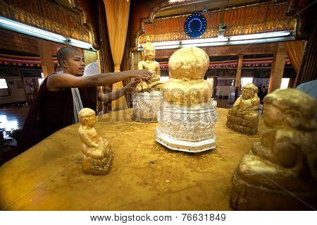 Buddhish Monk is gilding gold leaf at famous five small Buddhas