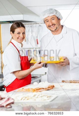 Portrait of happy chefs holding pasta tray in commercial kitchen