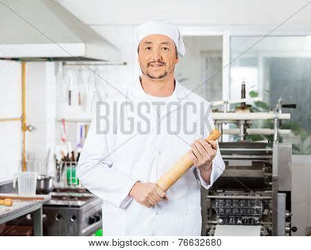 Portrait of confident male chef holding rolling pin in commercial kitchen
