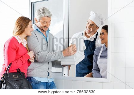 Happy couple buying uncooked pasta packet from chefs through window