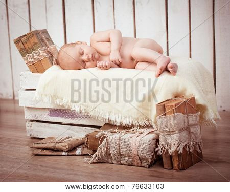 Newborn baby boy asleep among old books