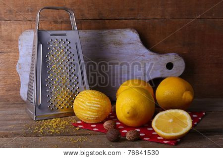 Lemons on polka dot napkin with nutmegs, grater and cutting board on wooden background
