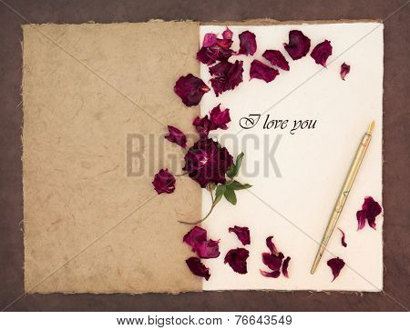 Old fashioned vintage notebook,with I love you phrase, ink pen and red rose with petals over lokta paper background.
