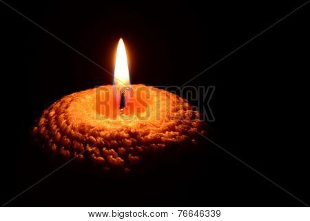 Yellow candle burning on a black background